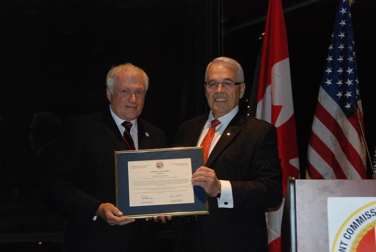 Commissioner Benoît Bouchard, right, thanks André Carpentier, left, for his service on the International St. Lawrence River Board of Control.