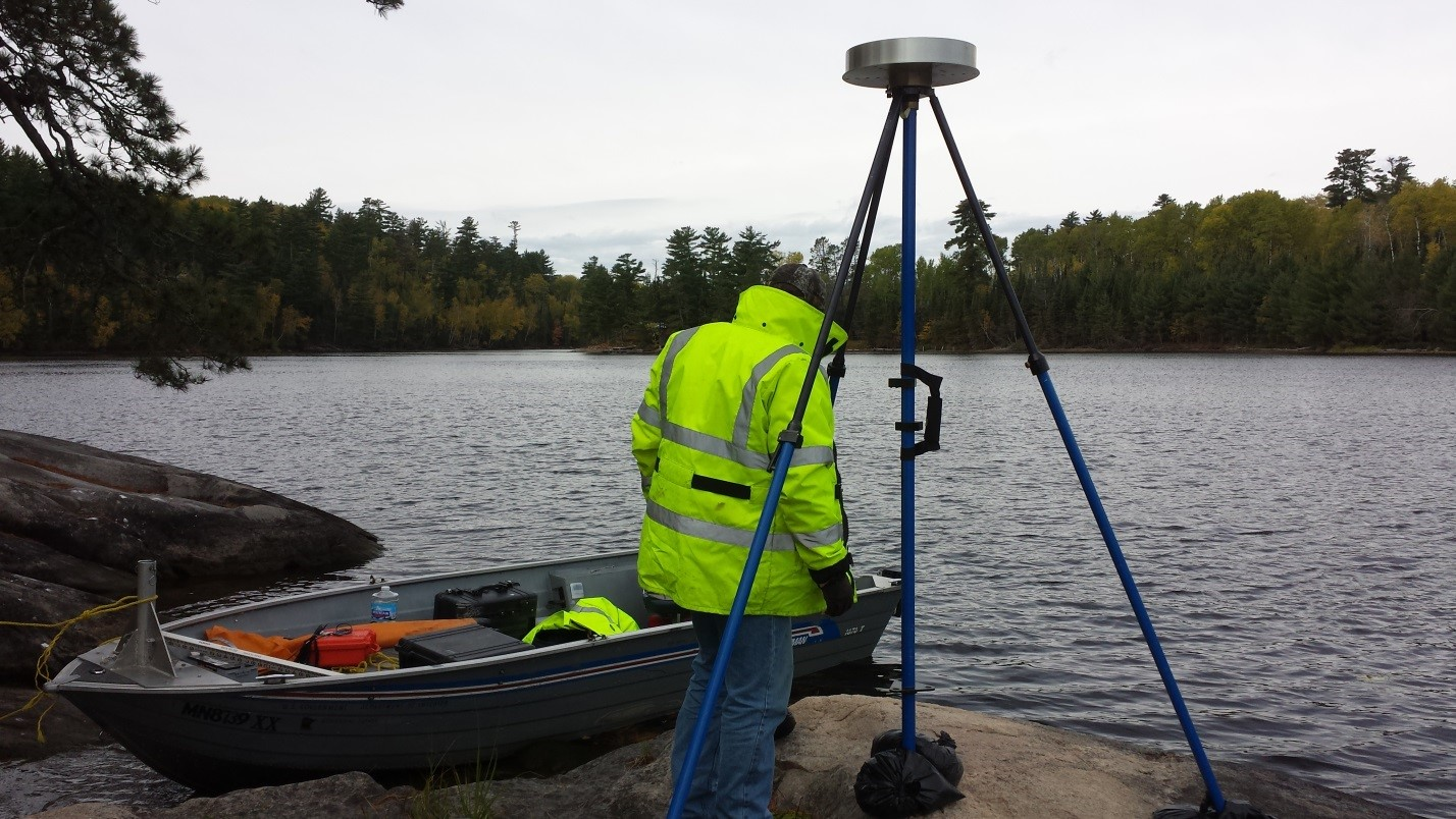 USGS Hydrologic Technician Justin Krahulik sets up surveying equipment off the lake shore. Credit:  U.S. Geological Survey
