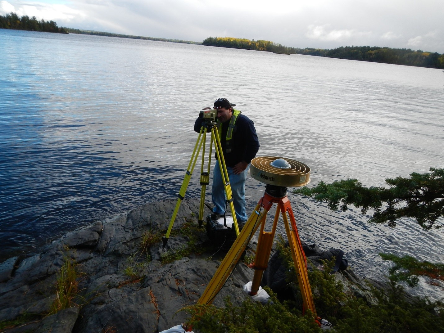 Natural Resources Canada Geodetic Engineer Jason Silliker uses survey equipment on the Rainy-Namakan Lake system to help standardize water level measurements. Credit: U.S. Geological Survey