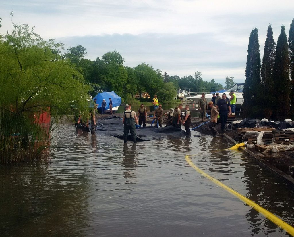 US Army National Guard members deploy a water-filled cofferdam by Sodus Point, New York, to help control Lake Ontario floodwaters