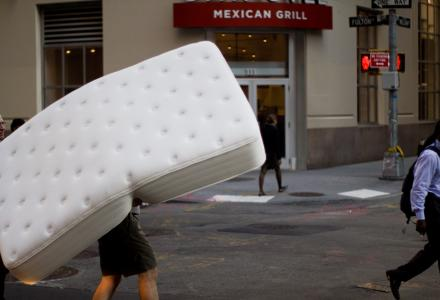 person carrying mattress
