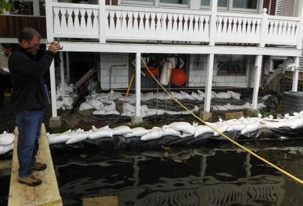 sand bags lined up in front of home along flooding Lake Ontario